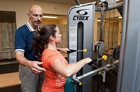 Manager of our Rehab and sports medicine facility working with at patient on a Cybex machine