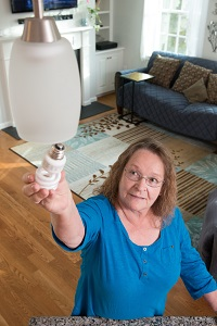 Lillian Racicot reaching for a light bulb after successful shoulder surgery