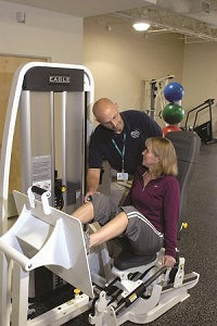 Rehab and sports medicine manager working with patient on equipment